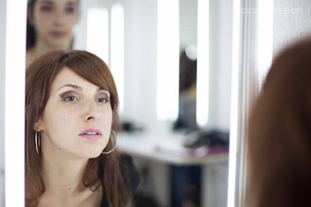 Mujer joven en espejo en curso de maquillaje