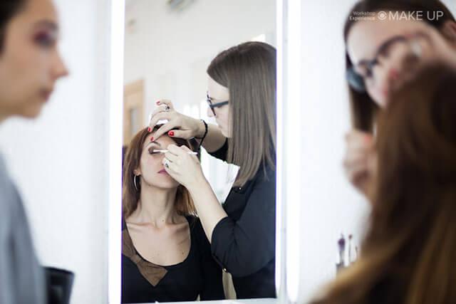 Maquilladora profesional trabajando frente a un espejo en una clase