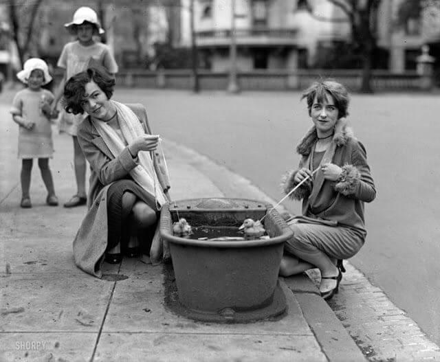 Mujeres bañando un par de patos en una bañera en la calle