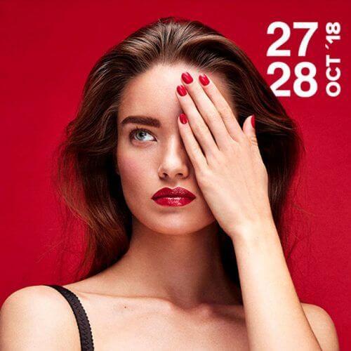 Chica tapándose el ojo con las uñas en color rojo