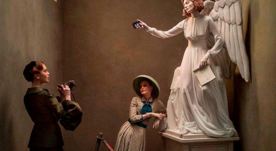 Dos mujeres tomando una foto a un angel