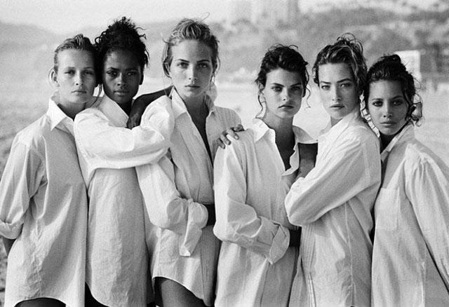 Seis mujeres vestidas con camisa blanca en la playa de malibú.