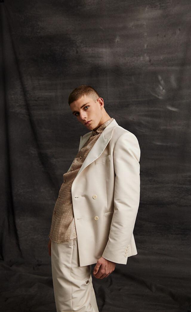 Modelo masculino con traje blanco.